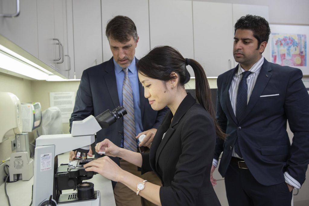 diverse research team, female researcher readys slide on microscope tray while two male colleagues watch