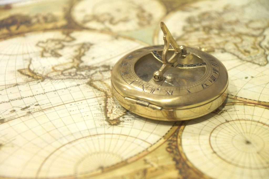 antique map of the world with brass compass and built-in sundial laying on the map