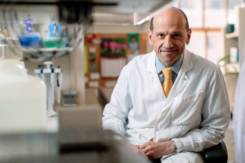Dr Vella, seated in his lab, faces the camera