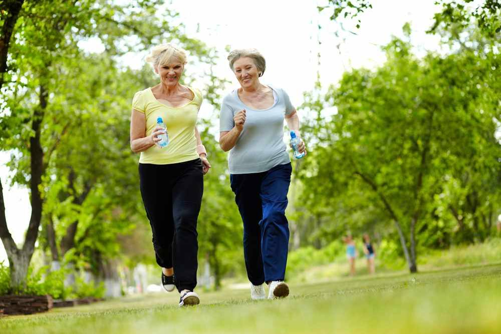 two older women walking outdoors for exercise, smiling, each holding a water bottle