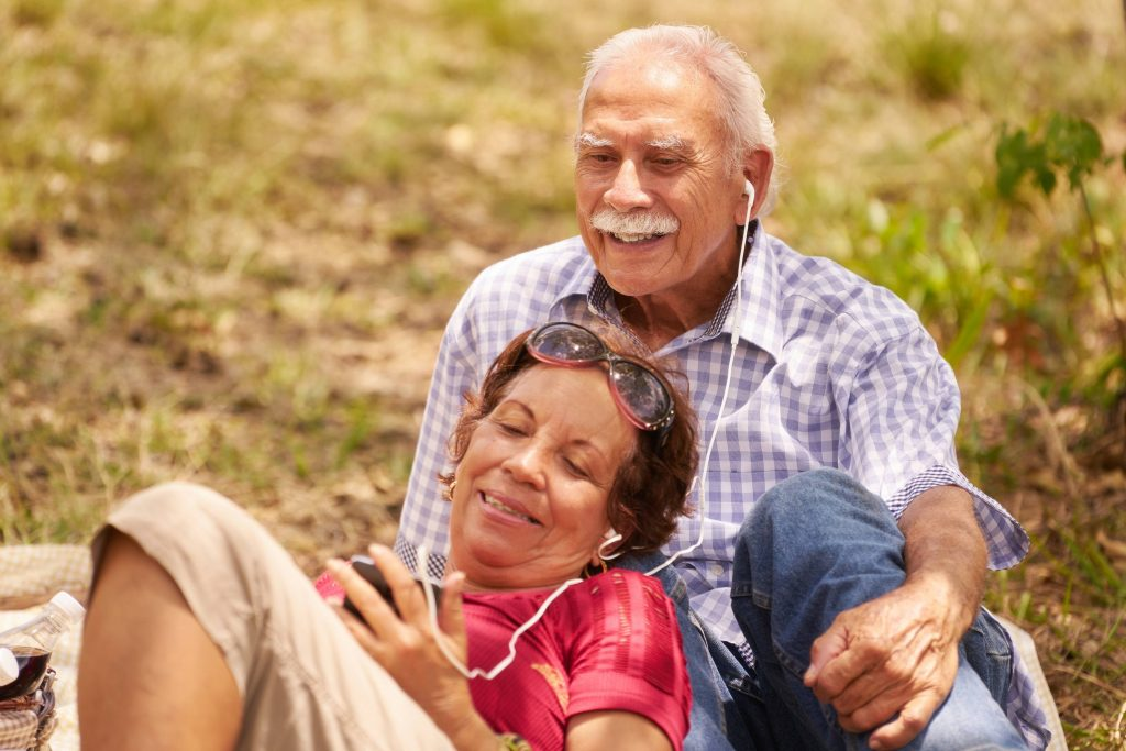 older couple relaxing on lawn, sharing a pair of earbuds connected to a phone