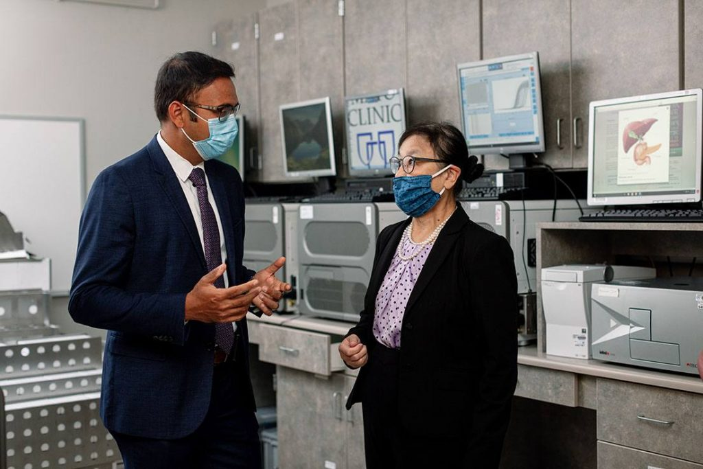 researchers in business attire, having conversation, male on left, female on right, in a laboratory setting, masked for COVID