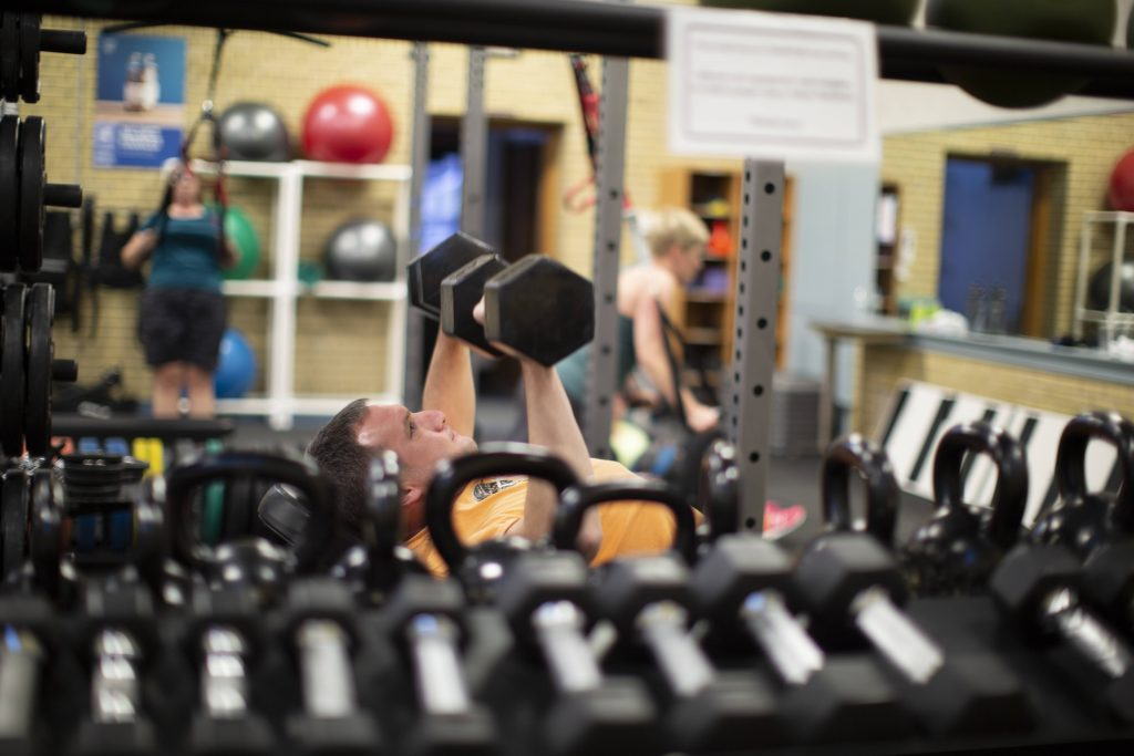 picture of several people working out in an exercise room, shot through a rack of hand weights