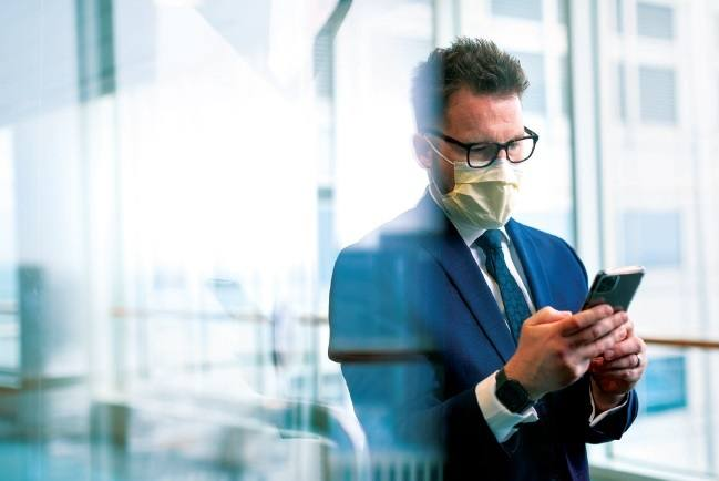 environmental image of Dr. Binnicker in windowed hall of Mayo Clinic, wearing mask during COVID-19, reading his phone