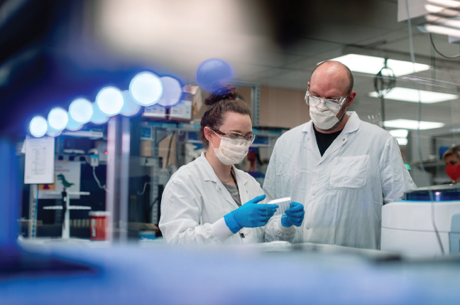 Lab environment during COVID-19. A female and a male lab employee examining an item. wearing lab coats, gloves, eye protection, masks