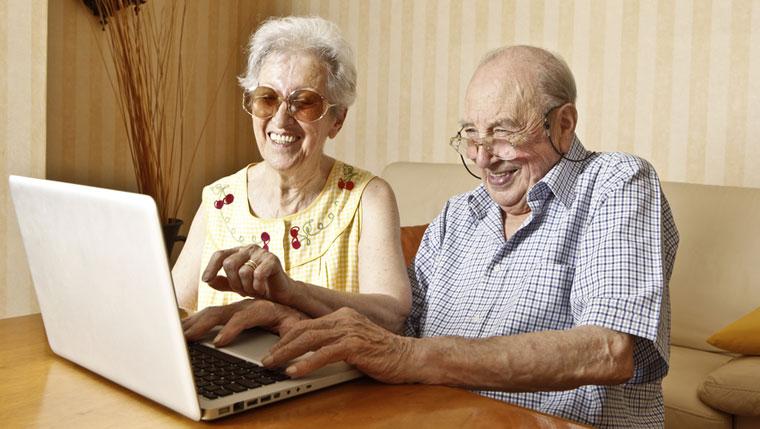 Elderly couple using computer.