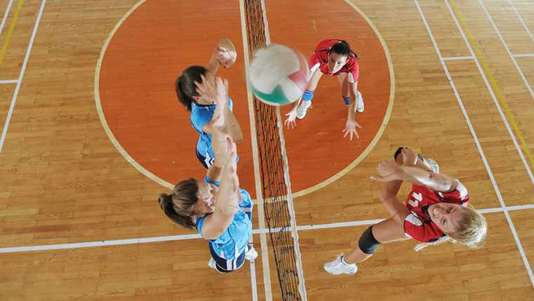 Volleyball players on court at net
