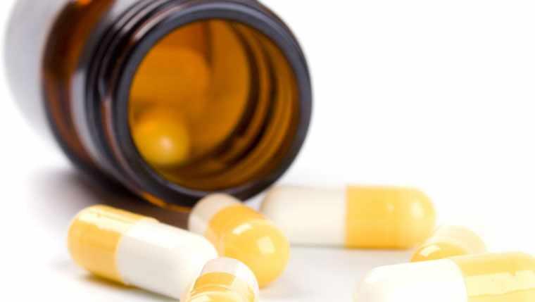 drug caplets outside of medication bottle