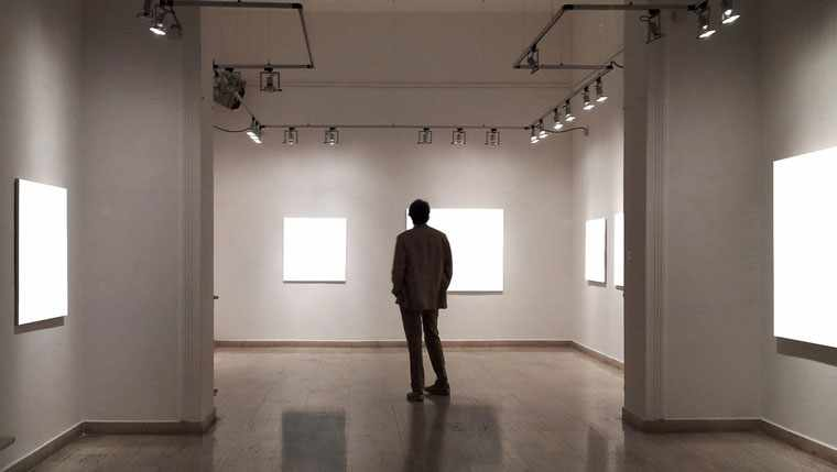 Man standing in art gallery with blank canvases on the walls