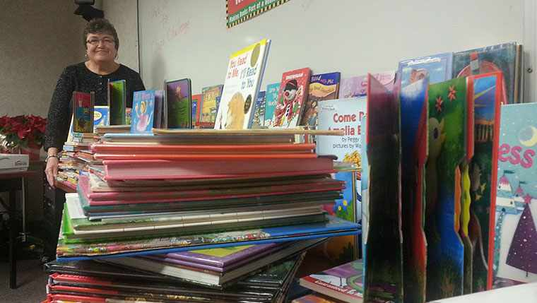 Kathy Chapiewisky beams with pride over the large pile of donated childrens' books.