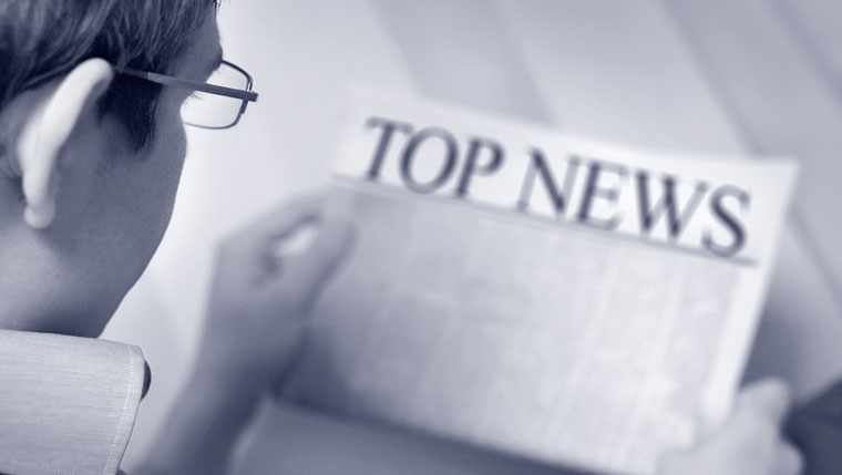 Man reads top news headlines in newspaper.
