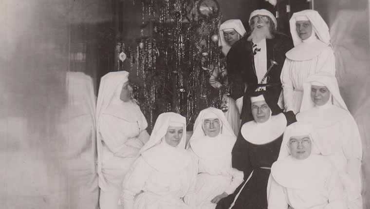 The Sisters of Saint Francis gather around the Christmas tree at Saint Marys Hospital in an archive photo.