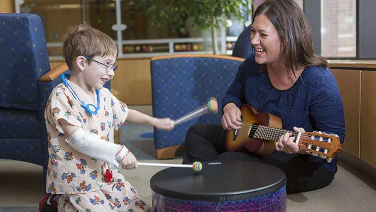 Christina would practicing some music therapy with a young patient.