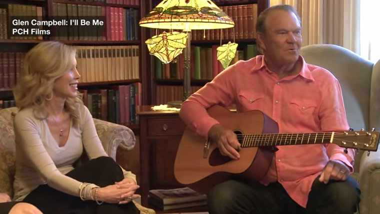 singer Glen Campbell playing his guitar with his wife Kim sitting nearby