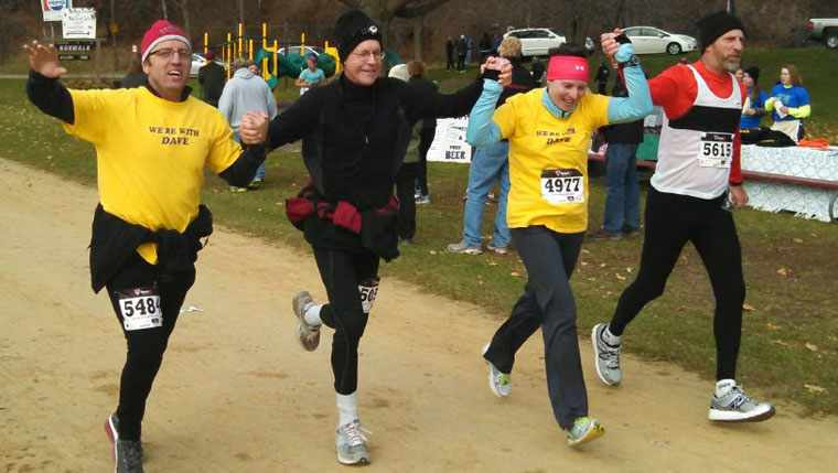 Dr. Dave Eitrheim running across race finish line holding hands with other runners