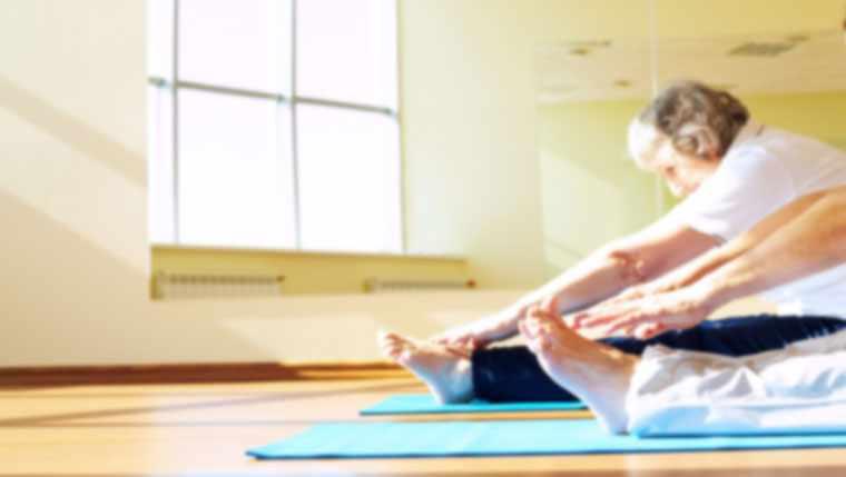 Elderly women doing stretches on yoga mats