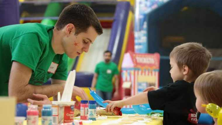Young adult man and a young boy playing with face paints