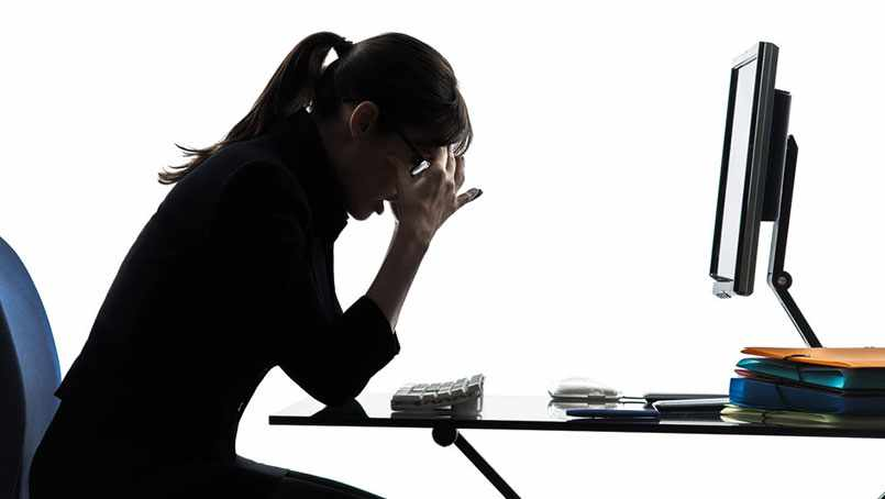 Image of woman at desk with headache.