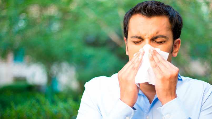 Man standing outside, blowing his nose into a tissue