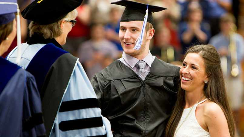 Chris Norton, with the assistance of his girlfriend, Emily Summers, walked across the stage to accept his diploma during Luther College's graduation ceremony.
