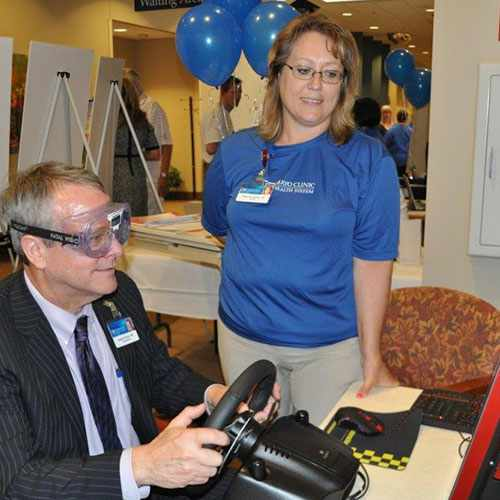 Greg Kutcher, M.D., president and CEO of Mayo Clinic Health System in the Southwest Minnesota region, tries the new distracted driving simulator.