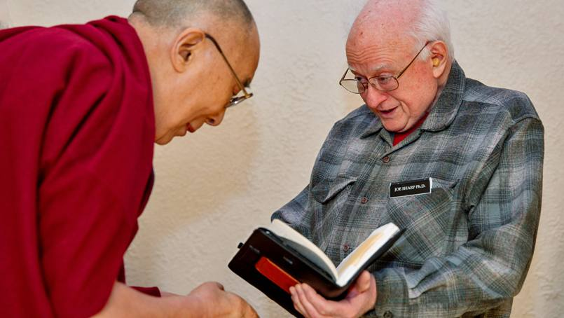 Joe Sharp, Ph.D., presents a copy of his wife's book to the Dalai Lama.