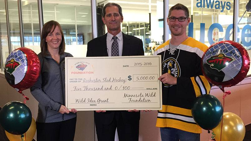 The Minnesota Wild Foundation presented a grant to the Rochester Mustangs Sled Hockey Team. Accepting the gift are Meegan van Straaten, Dr. Michael Stuart and Justin McClanahan.