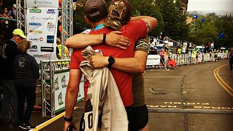 Travis Birr greeted by a fellow runner after completing the marathon.