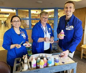 Two women and Merrick Ducharme, all in columbia blue volunteer jackets, poised to distribute acrylic paints from a cart full of craft materials.