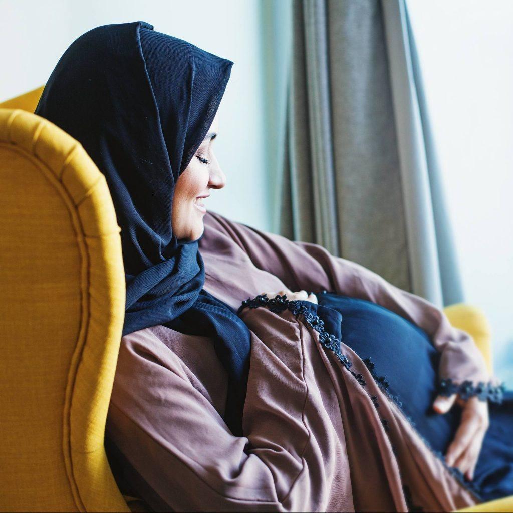 امرأة حامل شابة مبتسمة ترتدي الحجاب الشرعي، وتنظر إلى بطنها الحامل وتتلمَّسها.