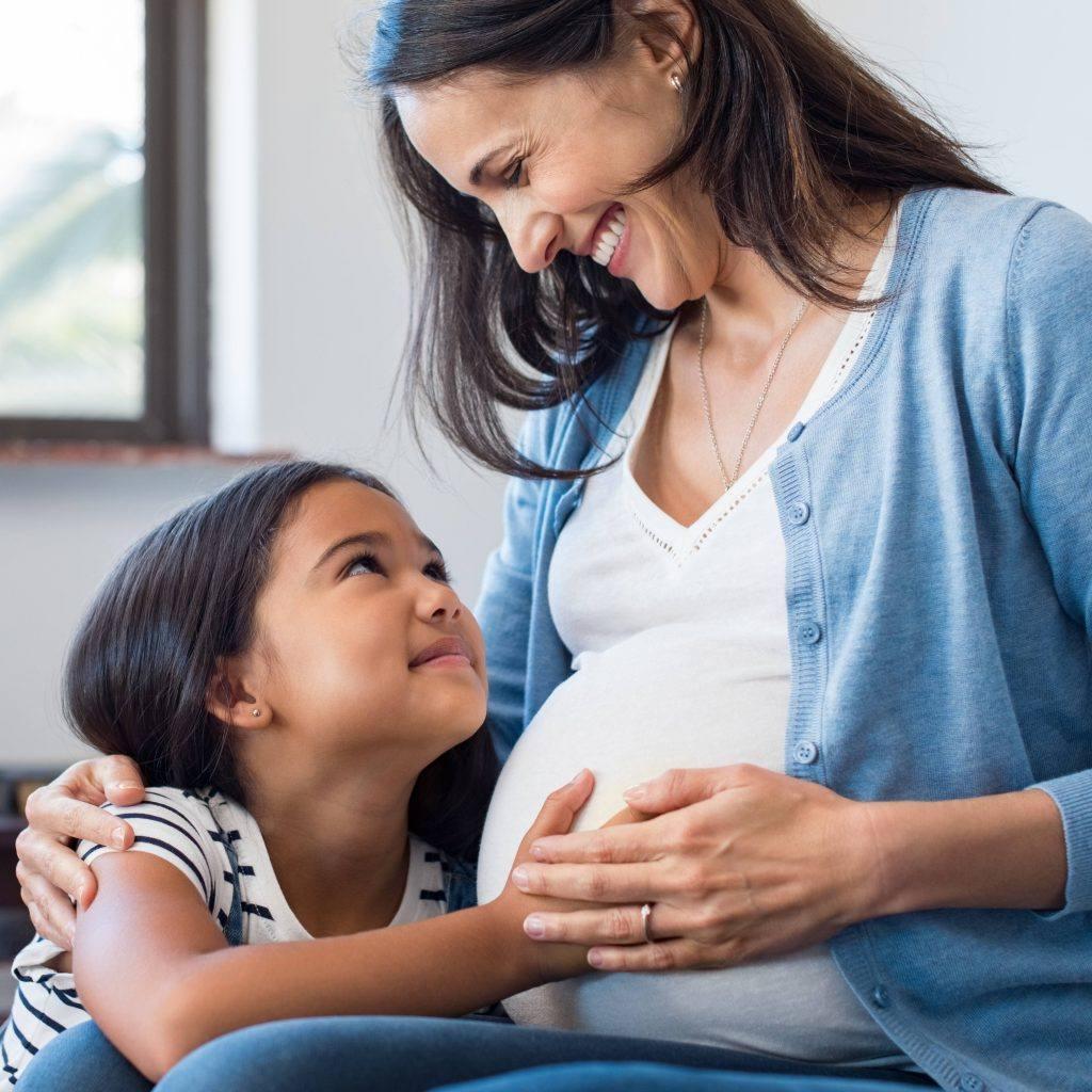 uma menininha tocando a barriga grávida de uma mãe
