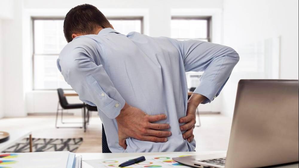 Homem de negócios à mesa com dor nas costas
