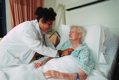 Nurse checking patient with a stethoscope