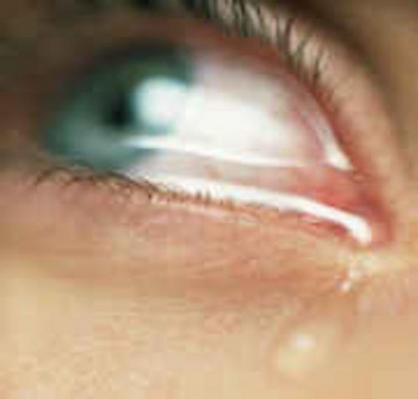 Close up picture of an eye with a tear falling out of the corner