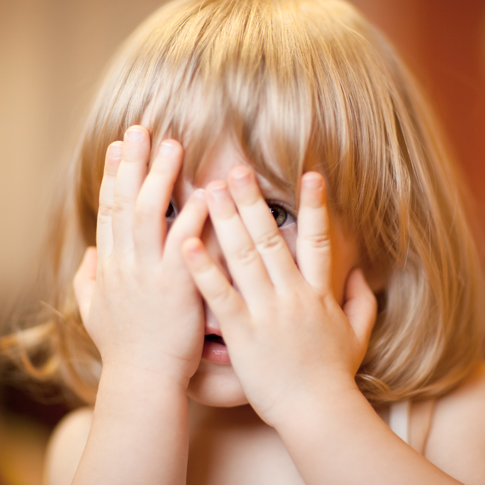 Little girl scared and looking through her hands