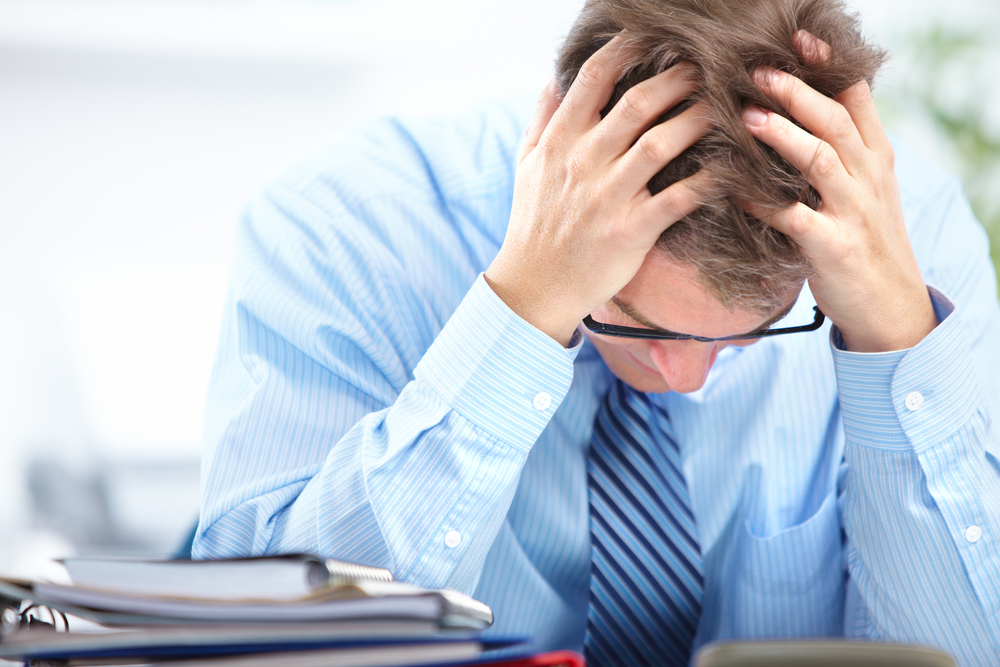 Man in blue shirt and striped tie with glasses holding his head with both hands like he has a severe headache