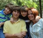 Jessica and her three boys outside together with green trees in the background