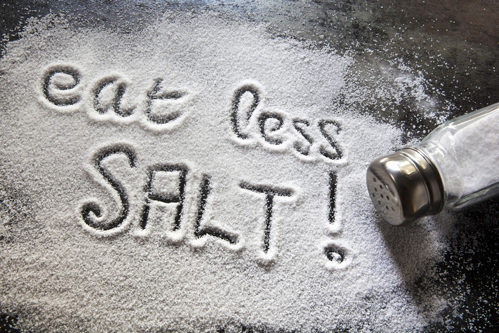 Salt shaker and words written 'eat less salt' in the spilled salt