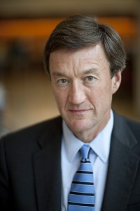 Mayo Clinic President and CEO, Dr. John Noseworthy in blue suit and striped tie