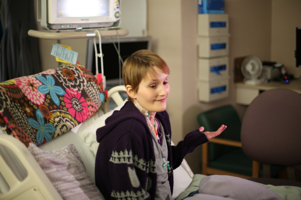 Jessica Danielson her hospital bed with flower blanket in background