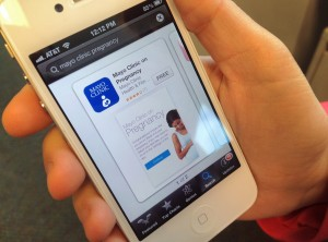 Person's hand holding iPhone with image of Mayo Clinic Pregnancy App