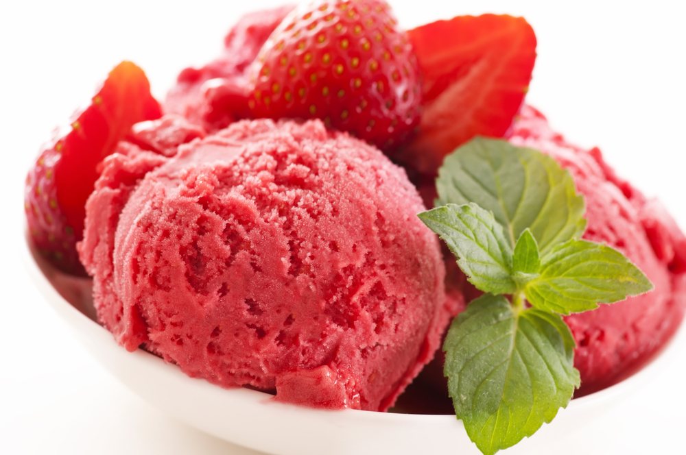White bowl of pinkish red strawberry sorbet with fresh sliced strawberries and sprig of green mint leaves