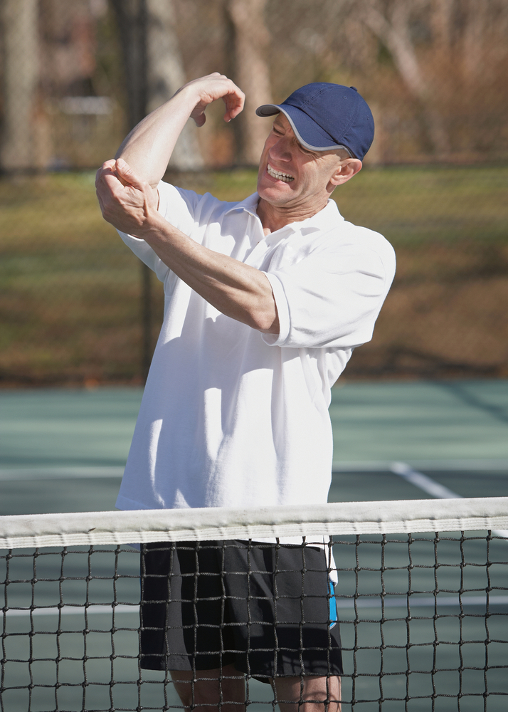 Tennis player with white shirt and blue cap on the tennis court holding his elbow