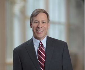 Mayo Clinic CAO Jeff Bolton in a gray suit and red striped tie