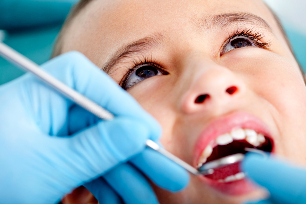 Young boy with mouth open and dentist in blue gloves is examining his mouth with dental instruments