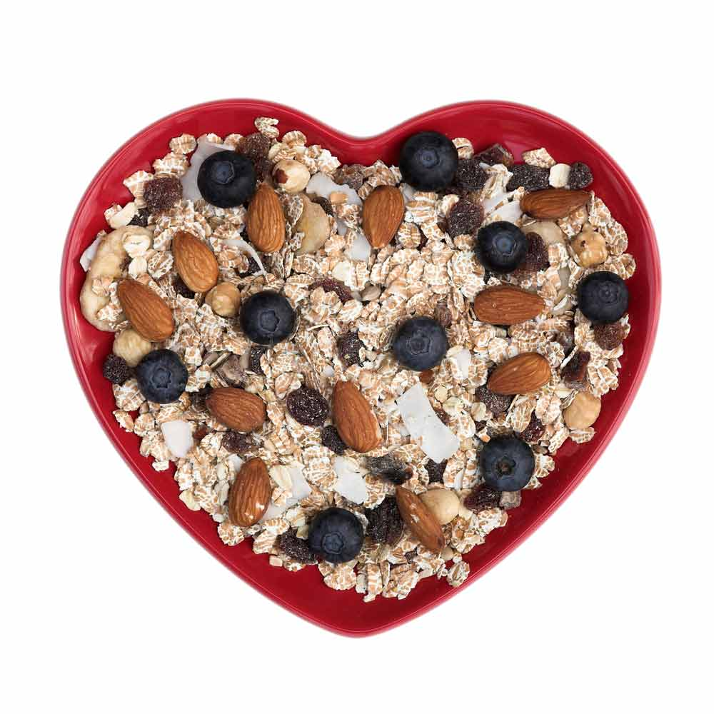 Heartshaped bowl of oatmeal, nuts and berries