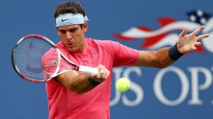 Blue U.S. Open background with tennis player Del Porto in white sweatband and pink shirt hitting tennis ball.