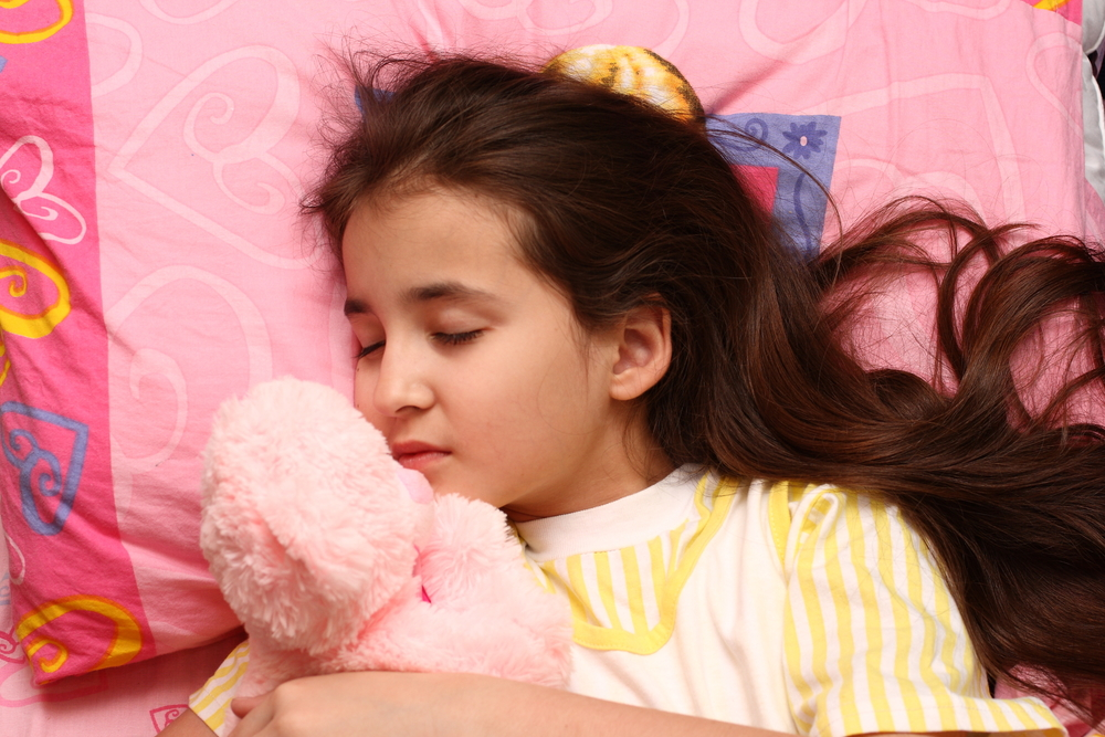 Little girl with long black hair sleeping on a pink pillow holding a stuffed animal