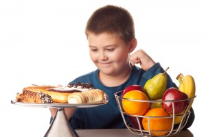 Boy is tempted by a plate of pastries.