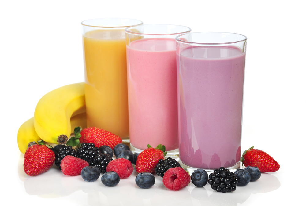 Three clear glasses of smoothie drinks - orange, pink, purple - with fruit around them